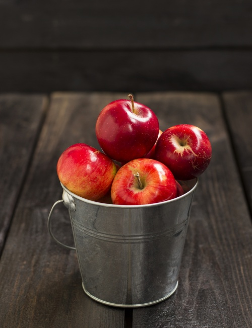 Crop of red apples in metal bucket on a dark wooden background