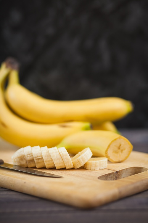 sliced banana with a knife on wooden board