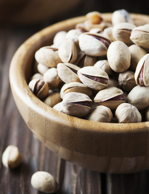 Salt pistachio nuts in the wooden bowl