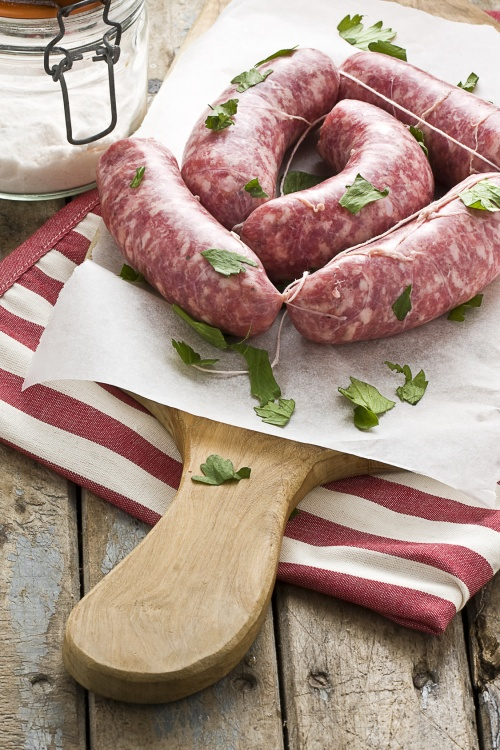 Raw sausages with herbs on baking sheet on catting board next to salt jar on rustic wooden table